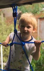 Climbing (tortipede) Tags: boy portrait playing garden 50mm prime child minolta ambientlight sony naturallight climbing oxford climbingframe fromraw f17 eastoxford a500 rawtherapee brunoscottbuck