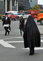 Hasidic Jew and Muslim woman pass in crosswalk, Park Extension, Montreal (Blake Gumprecht) Tags: woman quebec robe montre