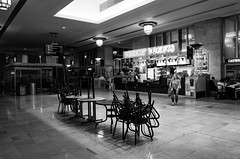 gawker (168) (Beau Finley) Tags: project365 365 project monochrome blackandwhite bw mono beaufinley philadelphia pennsylvania philly city urban 30thstreetstation train station amtrak septa woman donuts dunkindonuts chairs closed table ricohgrii ricoh ricohgr