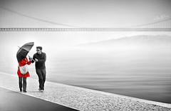 We Are In It Together (Ben Heine) Tags: life street city bridge red sea blackandwhite mist blur art love tourism portugal rain silhouette fog umbrella season landscape photography photo seaside scenery couple waves photographie pavement walk lisbon duo horizon pluie samsung lovers southbank amour urbanexploration instant capture anonymous paysage eternity brouillard share complicity badweather trottoir meteo amoureux parapluie almada waterscape complicit anonyme ondes selectivecoloring tejoriver 25deabrilbridge benheine suspendedstructure nx20 weareinittogether