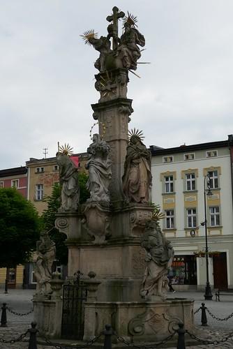 Pomnik Trójcy Świętej (1739-42, Klahr Starszy) na tle południowej pierzei w Lądku Zdroju