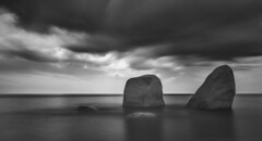 Boulders in the Sea (JamCanSing) Tags: longexposure sea blackandwhite sun storm clouds dark rocks surf ominous boulders infrared minimalist bnw nex6