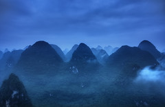 Blue Ridge Mountains (TheFella) Tags: china morning travel blue trees mist mountain storm mountains slr grass misty fog clouds digital photoshop sunrise canon landscape eos dawn photo high asia dynamic cloudy guilin yangshuo fineart hill chinese foggy peak stormy hills photograph processing limestone 5d thunderstorm bluehour dslr karst fareast hdr highdynamicrange southchina mkii guangxi markii eastasia  postprocessing travelphotography photomatix   thefella 5dmarkii  conormacneill thefellaphotography