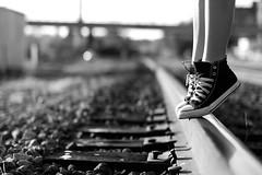 On the railroad (Noelle Buske) Tags: wood railroad bridge light shadow blackandwhite bw blur cute feet girl fashion standing train buildings dark dance focus shoes rocks legs bokeh dream style tippytoes sneakers jordan converse balance lovely traintrack balancing laces nopants ankles calves