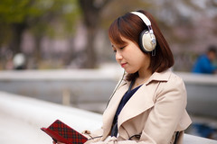 Japanese girl listening to music over headphones at park (Apricot Cafe) Tags: woman green girl japan walking outdoors tokyo spring sitting smartphone headphones cherryblossoms relaxation refreshing oneperson yoyogipark weekendactivities canonef85mmf18usm listeningmusic img631608