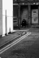 Away from the madding crowds (Philip Gillespie) Tags: road street door city people bw white man black monochrome hat lines canon photography grey mono scotland town cool edinburgh sitting break quiet peace phone may peaceful away hidden step resting exit tones 2016 sequent