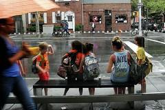 kid's shelter (omoo) Tags: streetscsnes westvillage greenwichvillage newyorkcity kidscamps children citycampers blonde girl leader shelter busshelter rain rainy raining hudsonandbarrow dscn9211 nyckidscamps kidsshelter umbrellas