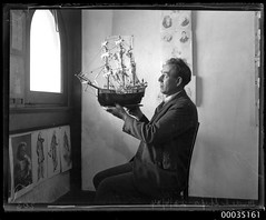 Man holding up a model of 16th century ship, 23 June 1934