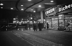 A news stand and coffee shop illuminated at night at the entrance to the car barns 1937 james crookall (vancouverbyte) Tags: vancouver oldvancouver vancouverarchives vintagevancouver