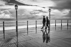 Braving The Elements (Explored) (Fourteenfoottiger) Tags: street light shadow sea sky people blackandwhite beach wet water monochrome lines sunshine rain weather clouds contrast reflections walking sussex coast pier seaside couple walk candid patterns stormy lamppost walkway boardwalk coastline stroll glassy strolling