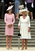 The Duchess of Cambridge aka Kate Middleton and the Duchess of Cornwall (right) stand for the national anthem during a garden party at Buckingham Palace London, England