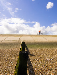 An orange t-shirt (kbee693) Tags: blue summer sky orange green beach clouds moss cyclist exercise timber pebbles groyne medway sheppey sheerness coastallandscape concreteseadefences