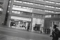 Rainy Day Leeds Street (Saturated Imagery) Tags: street people blackandwhite slr film 35mm leeds documentary reportage selfdeveloped prakticatl3 aph09 vivitar28mmf25 film:iso=200 fomafomapan film:brand=foma film:name=fomafomapan200 developer:brand=adox adoxadoluxaph09 developer:name=adoxadoluxaph09 filmdev:recipe=8073