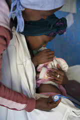 Health Extension Worker checks baby moges' breathing to determine improvement of pneumonia