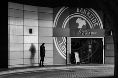 Bankside smoker (Spannarama) Tags: uk bridge light shadow blackandwhite man london sign arch tunnel smoking bankside southwarkbridge