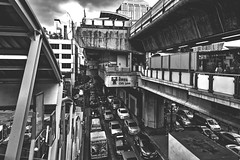 Chit Lom Station (KamrenB Photography) Tags: kamgtr kamrenb photography bangkok thailand thai city capital large massive buildings streets cars high tall asia sky concrete crowded dense people skytrain bts rail train road traffic siam black white gray grey grayscale greyscale faded chit lom chitlom bw grunge path walkway vehicles krungthep
