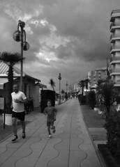 Runners (r_evolution63) Tags: street city boy sky urban bw italy cloud man monochrome sport clouds grey monocromo blackwhite europa europe strada italia nuvole grigio nuvola child cloudy sony perspective streetphotography overcast streetlife run bn persone uomo cielo esplanade promenade persons seafront lungomare bianconero compact citt ragazzo prospettiva bambino veneto jesolo lidodijesolo dscw7 correre provinciadivenezia jesololido chioscodoge 4550610112650483
