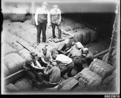 Crew men securing wool bales in the hold of MAGDALENE VINNEN