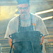 Chef Eddie Wilson works through the smoke while talking about cooking sides with Dutch Ovens.