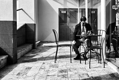 'Morning espresso and news ... ' (Canadapt) Tags: door morning shadow bw news man reflection portugal window coffee tile table chairs lisbon alfama canadapt