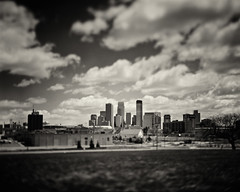 This is a photograph of a city, Minneapolis, in the daytime. [explored] (A Brand New Minneapolis) Tags: film skyline iso100 minneapolis 4x5 twincities rodinal tilt largeformat redfilter 135mm crowngraphic foma largeformatphotography minneapolisskyline graduatednd optar aristaedu100ultra dammelphotographicworks