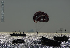 Parasailing into the sun.... (Uddhav Gupta) Tags: ocean blue sunset sea vacation sun india holiday man reflection beach sports water silhouette sport boat goa bleu watersports sparkling parasailing watersport