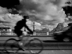 Travelocity (alex.illumidata) Tags: longexposure travel bridge blackandwhite sunlight blur london monochrome outdoors cyclist lifestyle kingston handheld shutterdrag x100