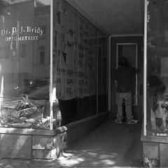 (patrickjoust) Tags: shamokin pennsylvania superricohflex kodaktrix400 developedinrodinal150 tlr twin lens reflex 120 6x6 medium format black white bw home develop film blancetnoir blancoynegro schwarzundweiss manual focus analog mechanical patrick joust patrickjoust usa us united states north america estados unidos autaut dj bridy optometrist office man standing old newspaper