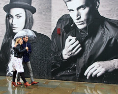 Young Couple - Oxford Circus (stevedexteruk) Tags: street west london wet westminster rain fashion umbrella canon advertising poster eos store clothing couple circus pavement os m h oxford advert end pedestrians billboards mm regent 600d 2013 1585