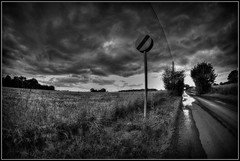 No sign of a change. (Steve.T.) Tags: road sky blackandwhite weather clouds landscape mono nikon dramatic wideangle stormy roadsign streetfurniture puddles dramaticsky essex littlebaddow samyang8mmfisheyelens d7200
