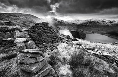 Mardale Life Mono (EXPLORED) (GraemeKelly) Tags: life winter sunset snow mountains monochrome canon landscape photography mono landscapes blackwhite nationalpark lakedistrict ruin reservoir snowcapped huts peat cumbria graeme kelly sunburst haweswater mardale graemekellyphotography