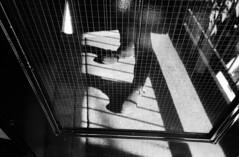 (flaxendream) Tags: door light blackandwhite sunlight reflection film analog 35mm grid bars shadows legs boots ricohgr1v