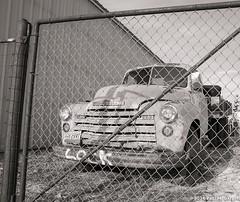 A Fence - A Truck (LostOzarkRambler) Tags: blackandwhite bw chevrolet monochrome truck fence montana 28mm chevy oldtruck chevytruck chevrolettruck nikond800