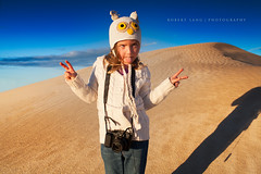 Young girl pulling silly face with camera around neck, sand dunes Australia (Robert Lang Photography) Tags: camera silly girl face horizontal female canon neck hilarious sand funny with dunes fingers stock young australia jeans around knitted beanie southaustralia pulling cardigan sanddunes oneperson portlincoln twofingers eyrepeninsula knittedtop owlbeanie canonpowershotg1x holdingupfourfingers holdinguptwofingers knittedsweatshirt