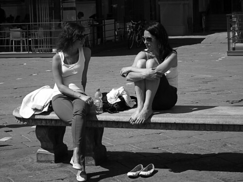 Two girls on a bench in the sun