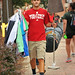 A student carries his shirts and lamp to his Central Campus residence hall.