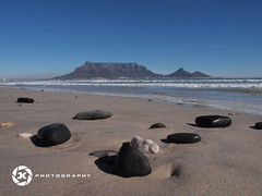 Volcanic Bebbles On Cape Town's Beach (jan-krux photography) Tags: ocean blue sea sky mountain beach water landscape volcano stones capetown e5 westerncape zd southaafrica 1260mm volcanicpebbles