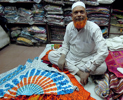 Old Fabric Seller (cowyeow) Tags: street city travel pink red india man smile shop businessman scarf happy clothing funny indian muslim islam traditional dude fabric friendly redbeard vendor scarves fruitstand rajasthan oldguy apparel streetvendor pinkcity thepinkcity
