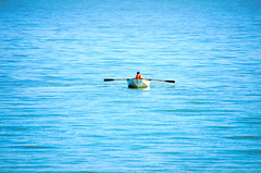 Boy rowing his boat out at sea. (photogeoff1) Tags: