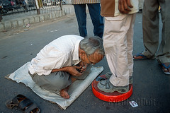 Senior man takes the weight of other people for a living, Ahmedabad, Gujarat, India (Cyrille Gibot) Tags: poverty street india man color colour men feet senior horizontal floor machine scene odd job weight gujarat ahmedabad weighing profession