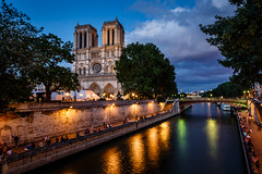 Notre Dame de Paris Cathedral and Seine River in the Evening, Paris, France (ansharphoto) Tags: city travel bridge blue vacation paris france building tower history church lamp electric seine skyline architecture night clouds facade river french temple lights evening town twilight ancient europe european catholic cityscape view cathedral dusk basilica religion gothic culture landmark medieval quay illuminated christian belfry romantic notre dame embankment cite noter