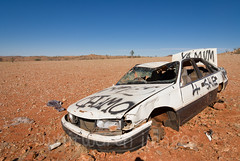 Wrecked Car (whitworth images) Tags: auto old blue red white abandoned car trash graffiti sand desert nt australia vehicle outback remote smashed wreck plain arid wrecked ruined dumped gibber