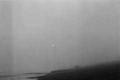 heavy (fotobes) Tags: sea blackandwhite mist beach monochrome 35mm blackwhite brighton surfer grain olympus om10 negativespace surfboard brightonbeach ilforddelta400 olympusom10 seafret
