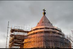 De koperen ploert belicht het roodkoperen dak