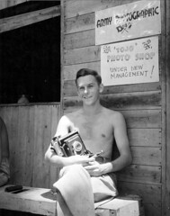 Sgt. Robert R Brenner, USMCR in front of the US Army Signal Corps photographic laboratory on Guadalcanal Solomon, IS.   Location: Guadalcanal, Solomon Islands. Unknown. (HarryKidd) Tags: camera usmc movie photography wwii photographers ww2 marines combat worldwar2 pacifictheater