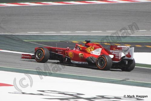 Fernando Alonso celebrates winning the 2013 Spanish Grand Prix, waving the Spanish flag