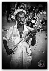 Man playing Indian folk music on Chikara (typical Rajasthani musical instrument) (FotographyKS!) Tags: poverty road street travel portrait people blackandwhite bw music india lake playing art face saint closeup rural religious temple person photography town blackwhite looking adult god market outdoor expression indian traditional religion creative culture streetphotography lifestyle instrument worker karma turban mustache spiritual pushkar hindu hinduism hardwork cultural pilgrim mandir rajasthan ajmer ethnicity chikara ghats selectivecolor photogrpahy poorman seniorman kreative pushkarlake streetsofrajasthan photoborder brahmamandir indianfolkmusic kreativeart pushkarsarovar