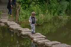 stepping stones (stevefge) Tags: china shanghai street people kids kinderen children boys park water crossing reflectyourworld reflections