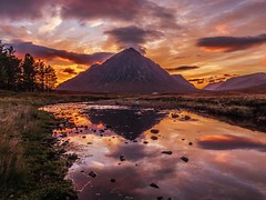 Buachaille Etive Mor at Sunset (Bathsheba 1) Tags: uk light sunset orange sunlight mountains west nature night clouds reflections spectacular landscape evening scotland still scenery rocks colours view purple cloudy eveningsun patterns scenic dramatic vivid escocia surface calm symmetry vista glencoe naturalbeauty dappled cloudscape schottland moorland ecosse munro scozia scottishhighlands naturalmirror buchailleetivemor kingshousehotel 2013 scottishglen riveretive canonpowershotsx50hs vision:mountain=0566 vision:sunset=0881 vision:sky=0968 vision:outdoor=0693 vision:ocean=0512 vision:clouds=09