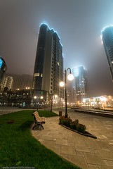 Fog in the city (Anton_ua) Tags: city blue sky urban mist tower window glass grass fog architecture night facade skyscraper buildings bench outdoors europe downtown technology exterior contemporary district background scene structure business backgrounds lantern futuristic